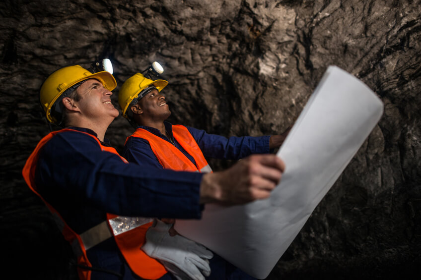 Miners working at the mine holding a blueprint